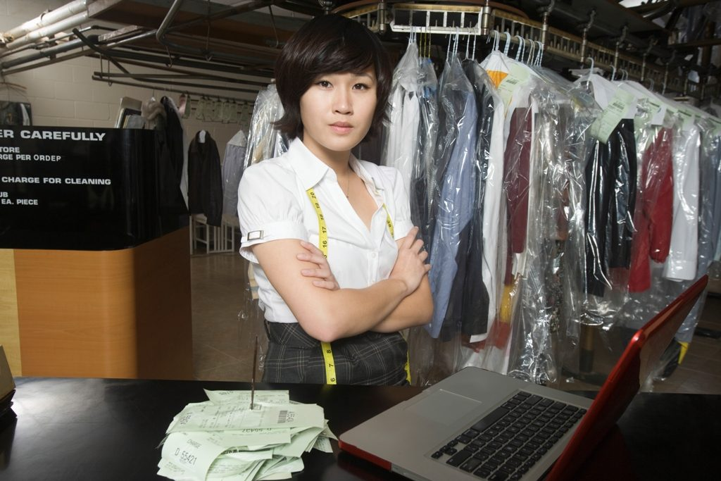 Confident Woman With Receipt Spike And Laptop On Counter In Laundry