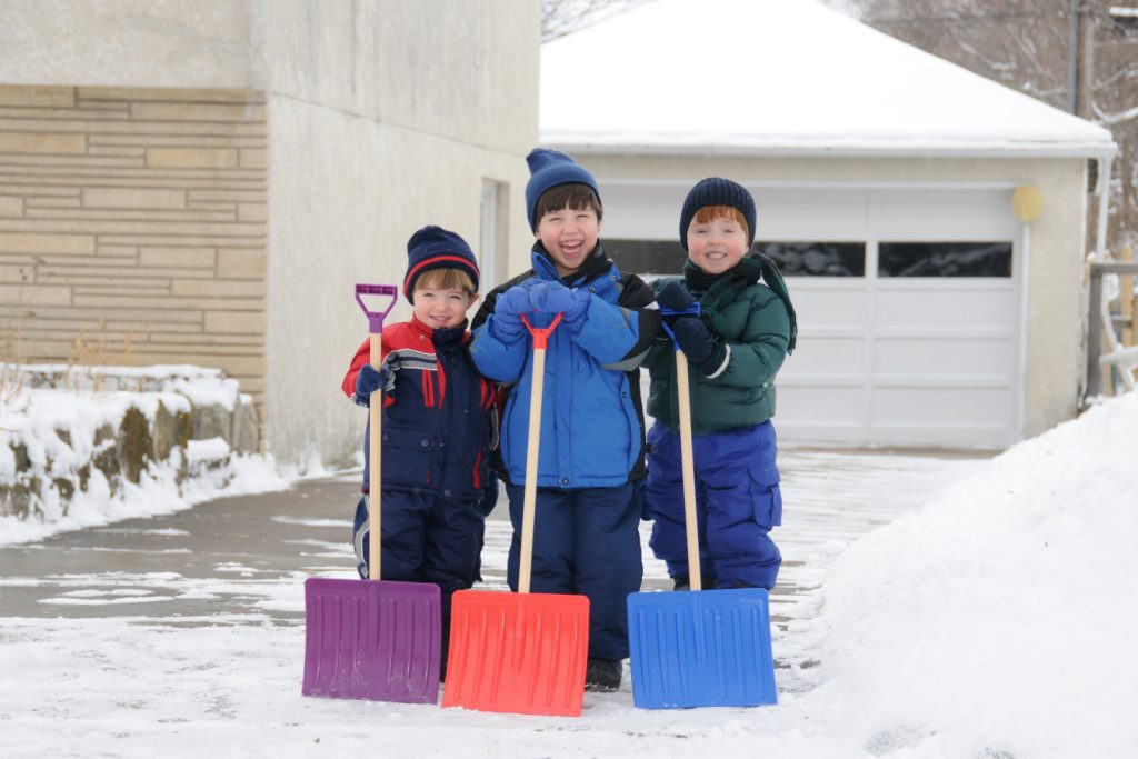 Three young boys take pride in completing a big shoveling job