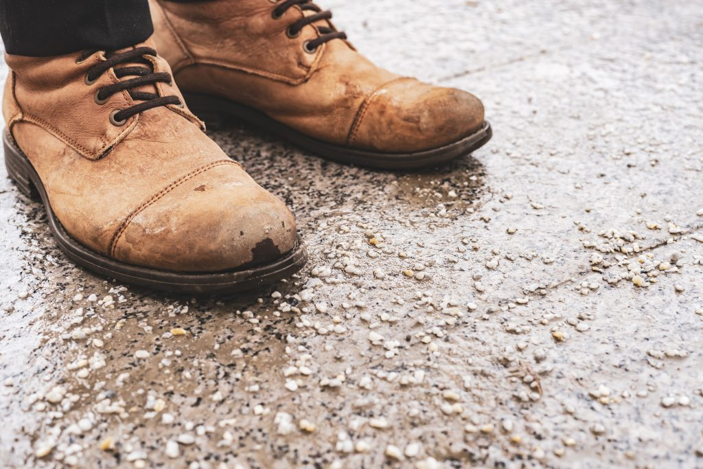 damaged persons shoes on salted pavement in the city during winter season