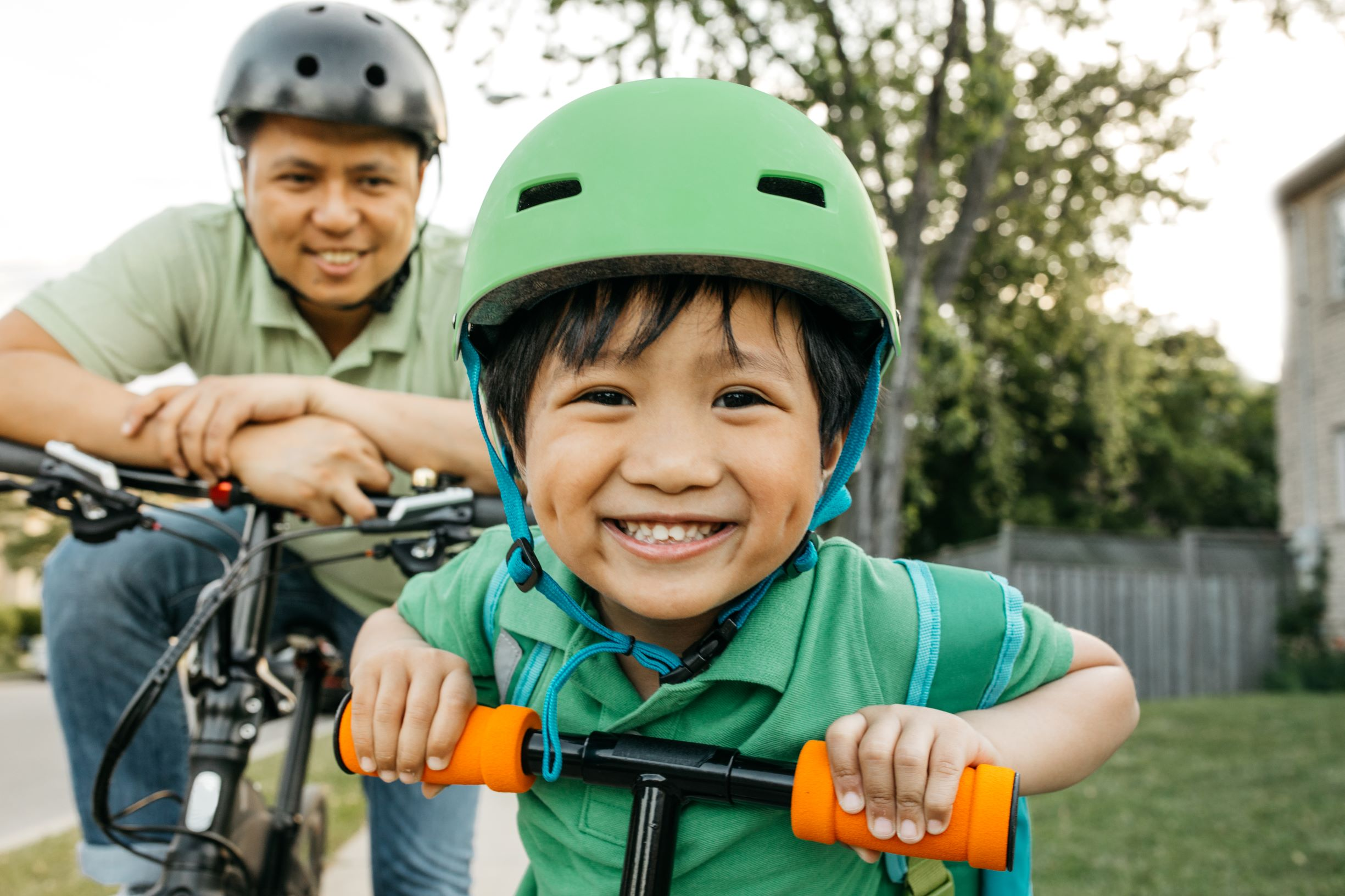 a child riding a bike grins happily at the camera
